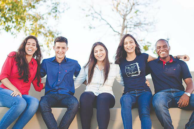 5 people sitting on a bench smiling and laughing